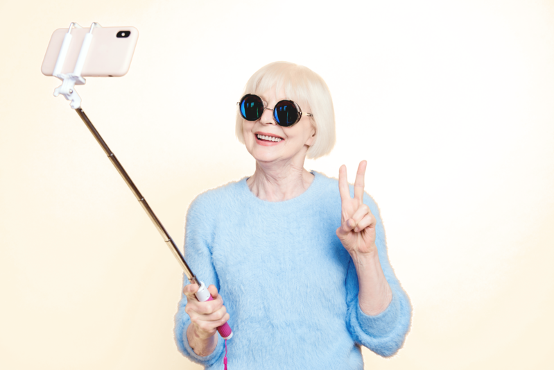 Woman with sunglasses on making a peace sign in front of a selfie stick